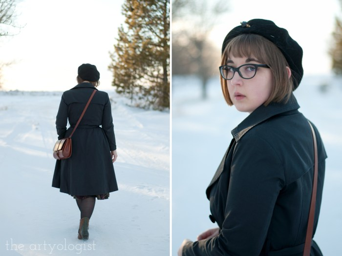 a lady wearing a black trenchcoat and beret walking down a snowy lane