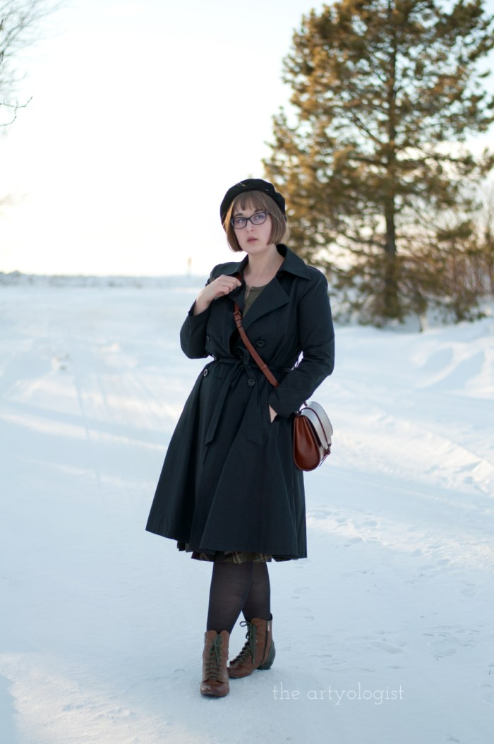 a lady wearing a black vintage styled trenchcoat and beret on a sunny winter day