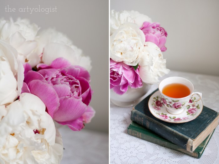 closeup of a peony bouquet, and a floral teacup on top of antique books