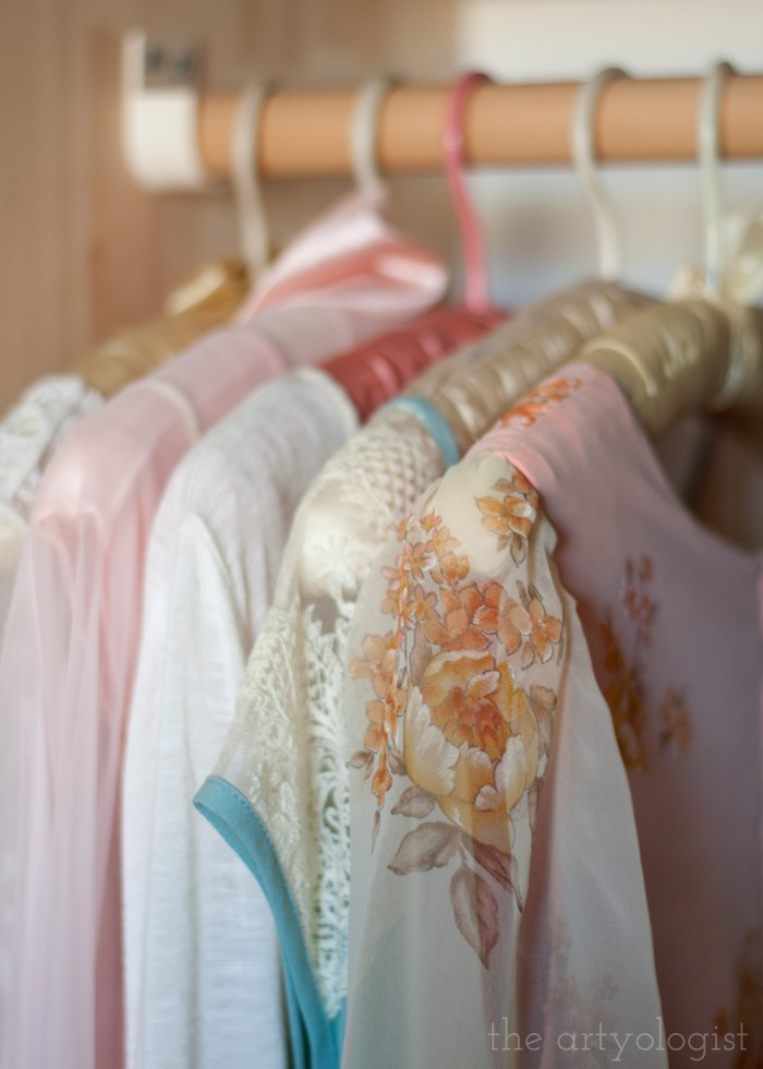 a row of dresses hanging in a closet on vintage hangers