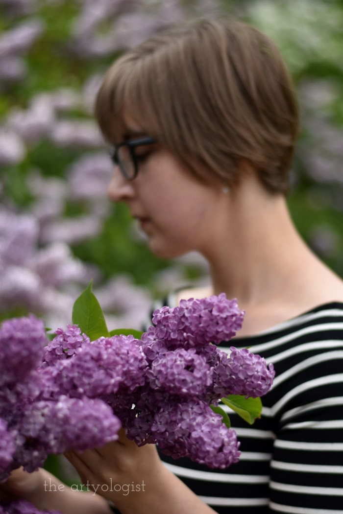 holding a bunch of lilacs