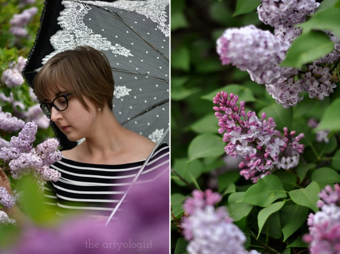 woman holding a parasol in front of a lilac hedge