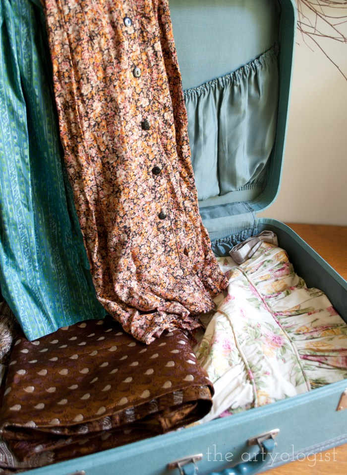 open vintage suitcase full of clothes