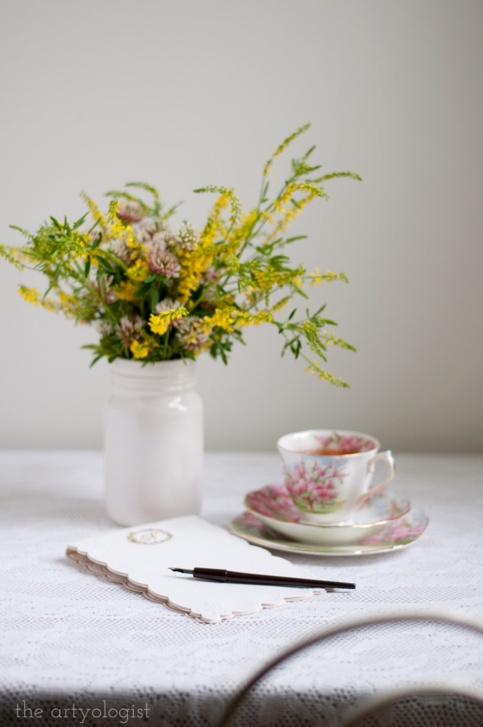 a desk with stationery in front of a bouquet of sweet clover and a cup of tea