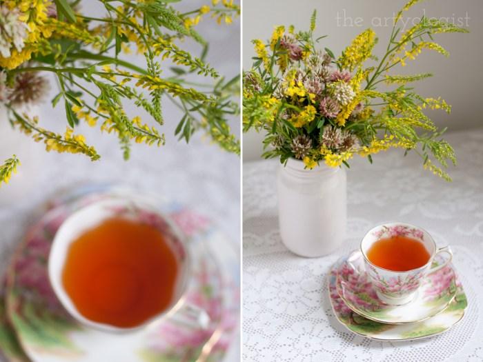 a lovely cup of tea beside a bouquet of clover