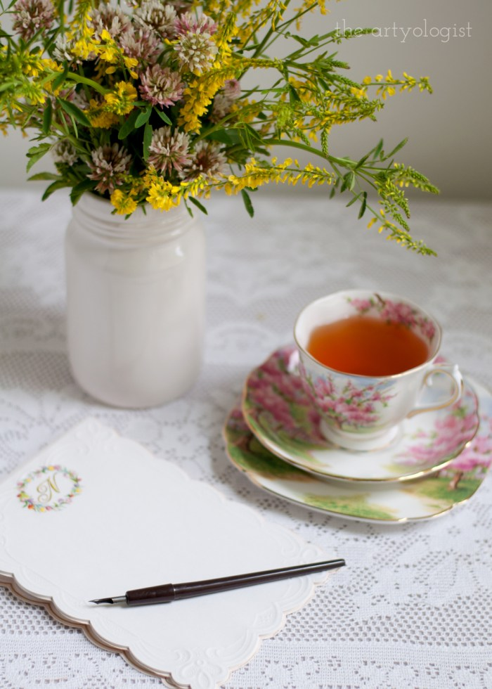 writing a letter at a desk with a cup of tea beside the pen and paper