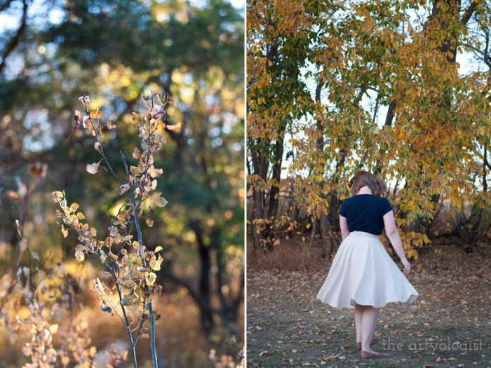 woman twirling in front of autumn trees