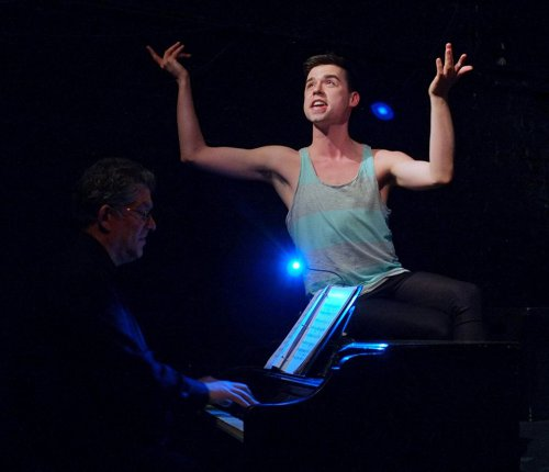 "Benjamin Dreier atop of the piano in a scene from ""Mad About the Boy"" (Photo credit: Jonathan M. Smith)"