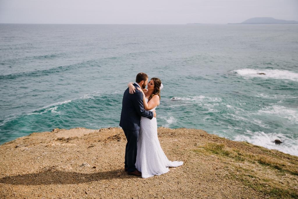 Bride and Groom hugging on lookout in Port Macquarie