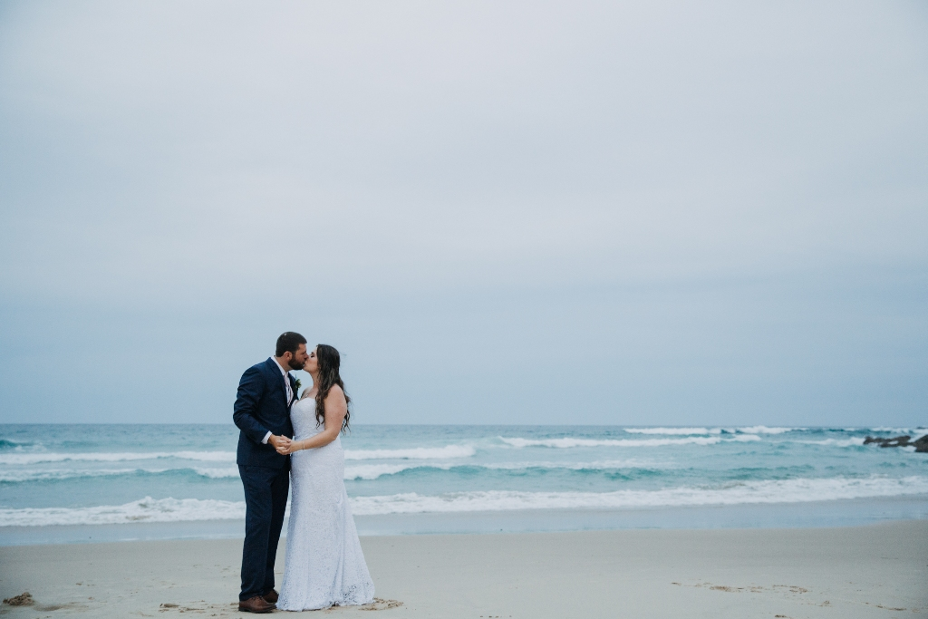 Bride and Groom kissing on beach at dusk
