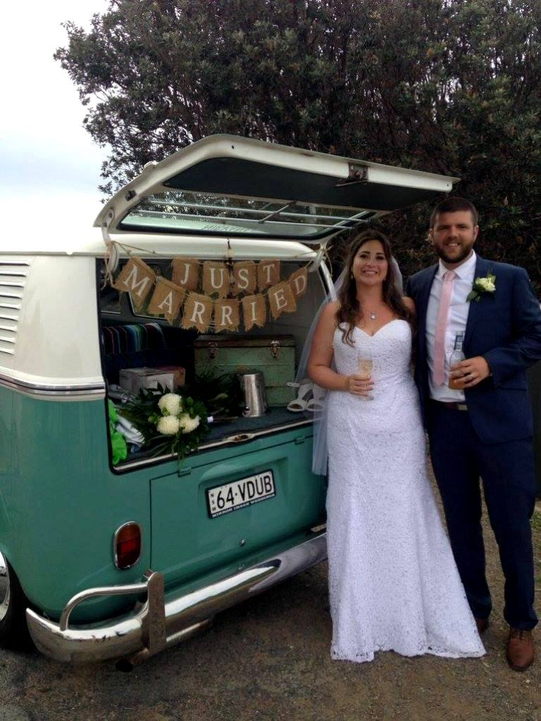 Bride and Groom standing in front of Just Married VW Kombi sign