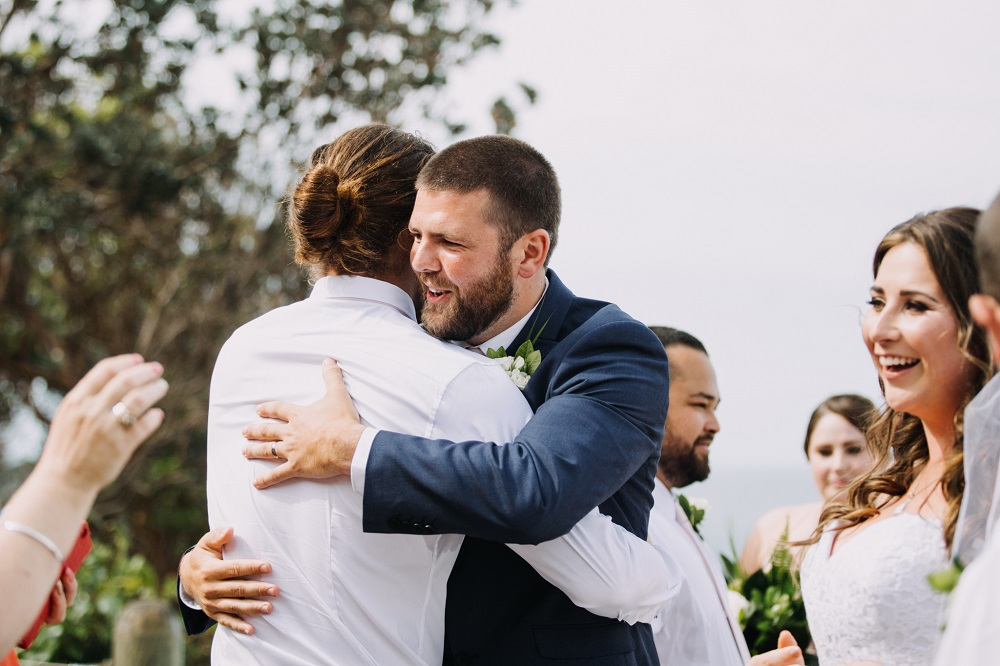 Groom and groomsmen hug after wedding