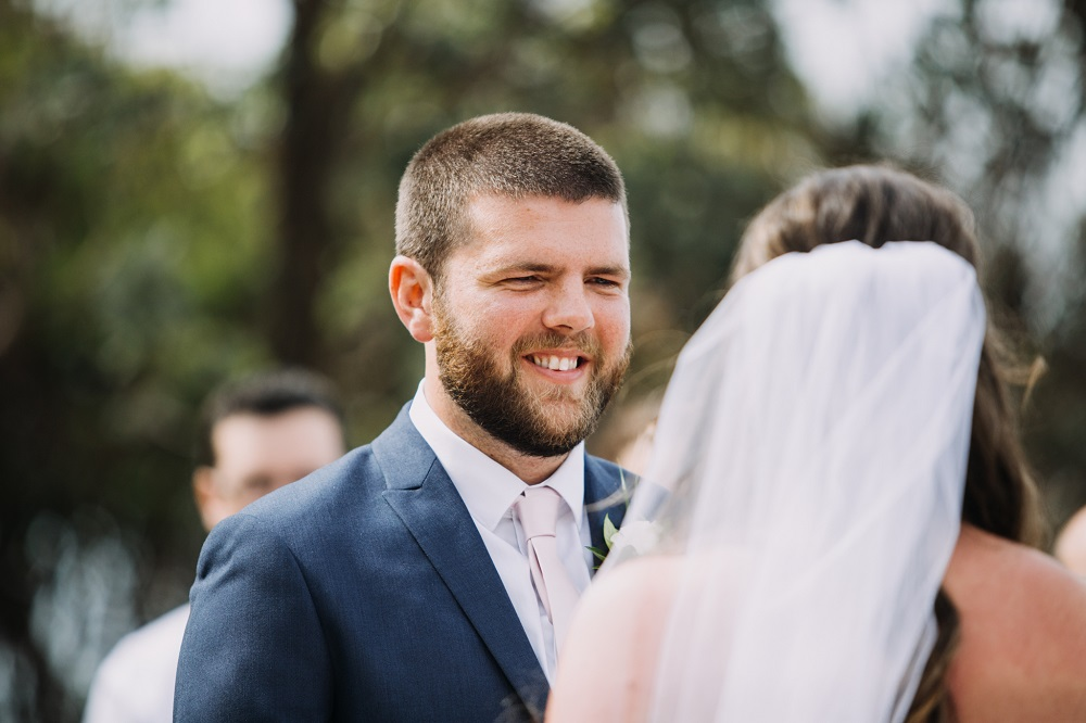 Groom smiling at bride