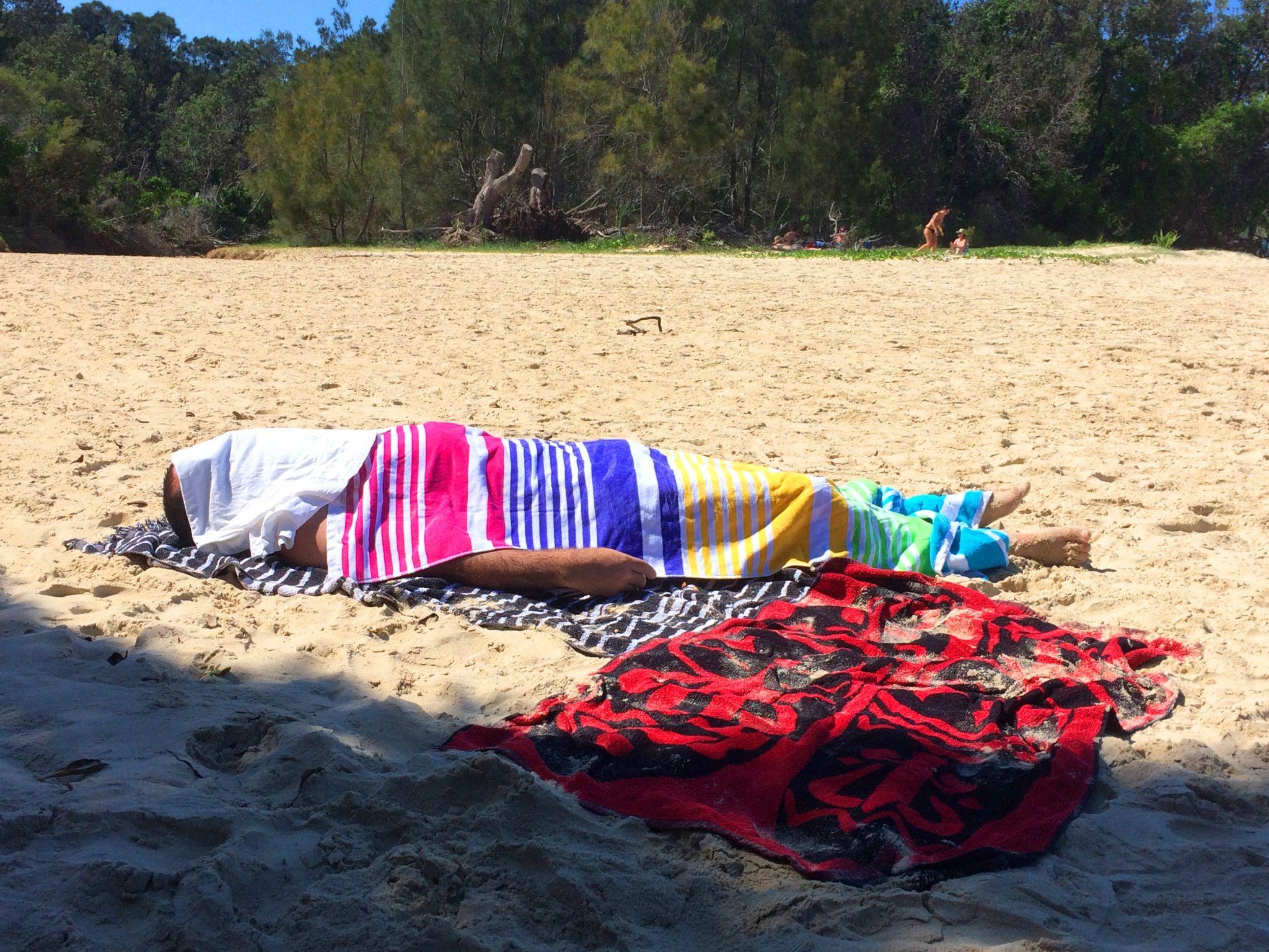 Sleeping under towels on beach