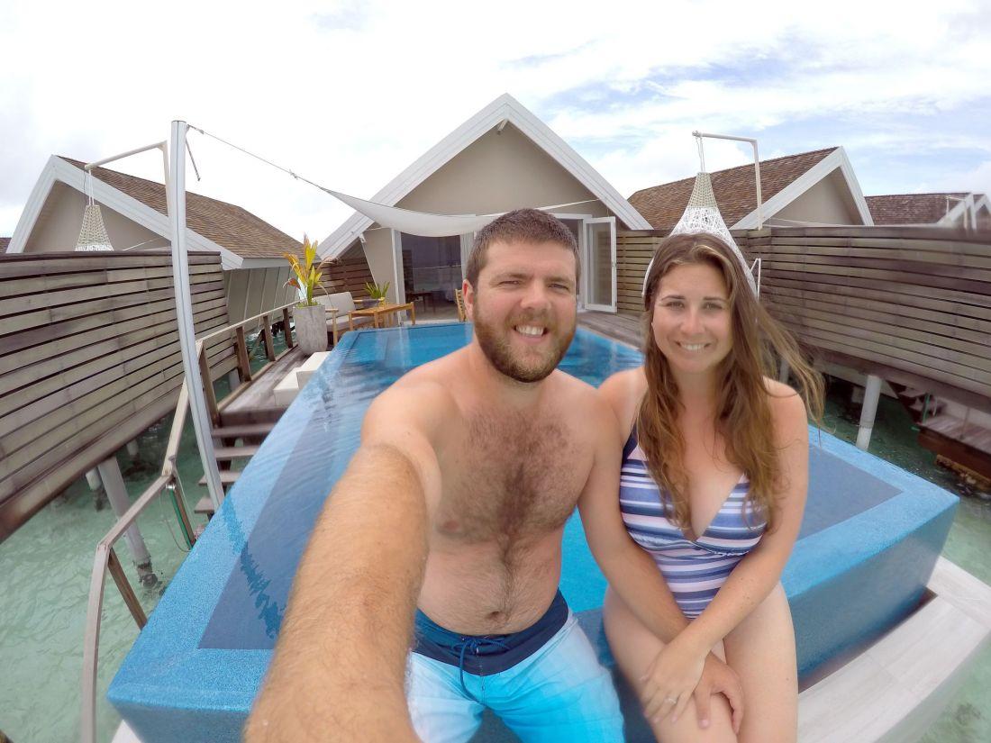 Couple sitting on infinity pool edge LUX Maldives