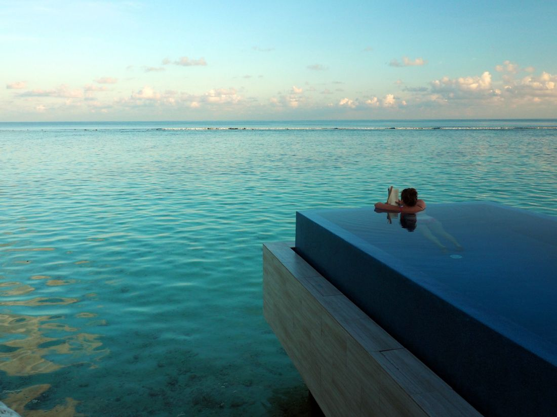 Reading in infinity pool LUX Maldives