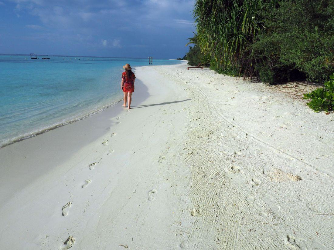 Girl walking on beach LUX Maldives
