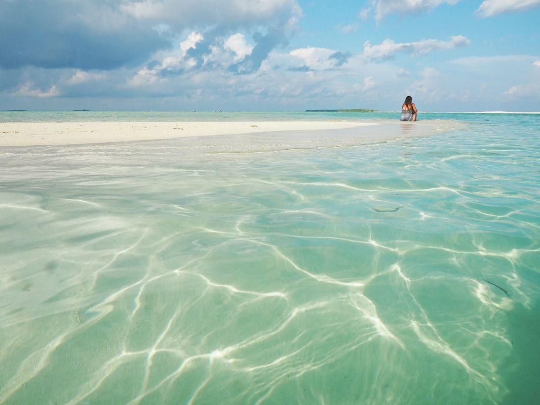 Simone sitting on sandbank in Maldives