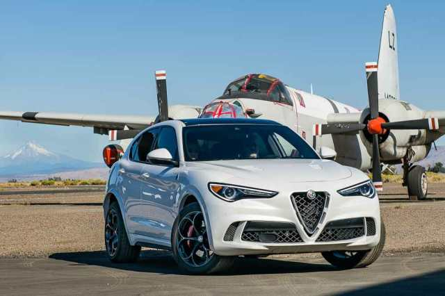 The 2019 Alfa Romeo Stelvio Quadrifoglio poses in front of an old airplane during Run to the Sun.