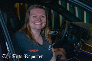 Winner of the BMW for a week, DirtFish worker smiles for the camera at Beauty & Key's launch at The Shop - The Auto Reporter