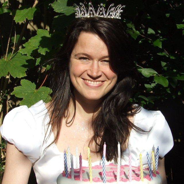 blogger ulla lake dressed as a princess holding a cake