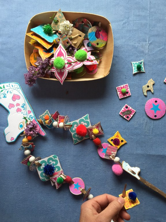 kids thread cardboard shapes onto ribbon to create colourful and sustainable junk necklaces
