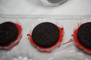 Place an Oreo on top of the melted chocolate and gently press down