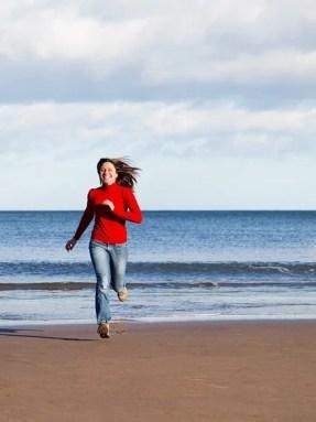 happy woman running beach