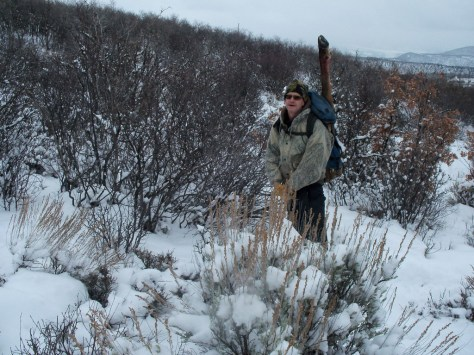 A solo hunter packs out a heavy elk hindquarter in the snow in colorado