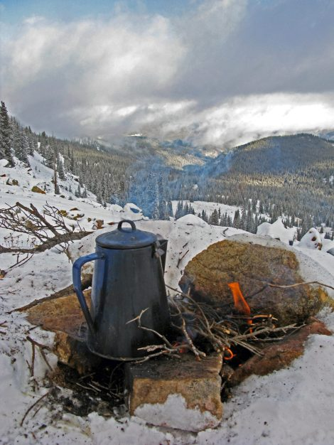 The pleasures of making cowboy coffee on the trail and in the backyard. Enamel coffee pot on the fire in the snow on an elk hunting trip.