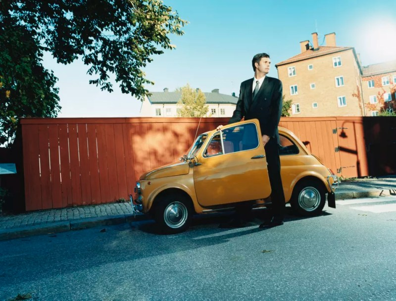 Business man standing next to a small car