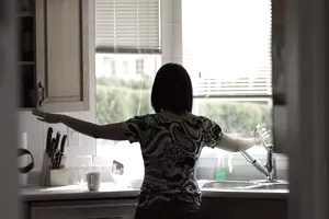 Woman turning on faucet at kitchen sink and shutting cabinet