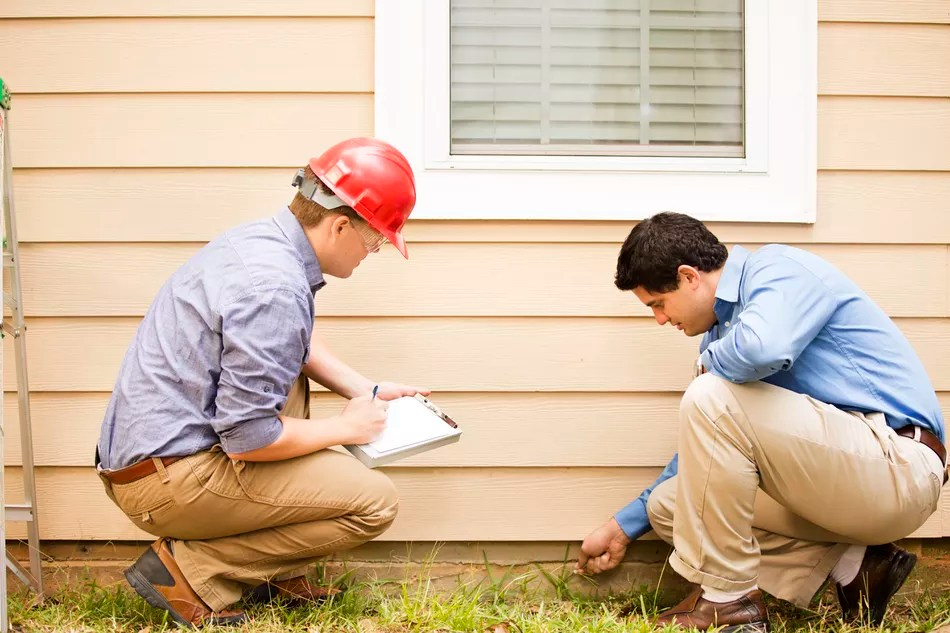 A home inspector with client looking at siding and foundation of a home