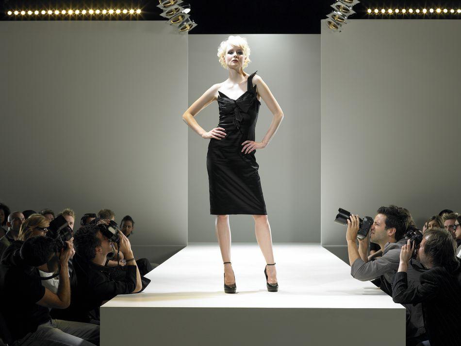 Paparazzi photographing fashion model on catwalk