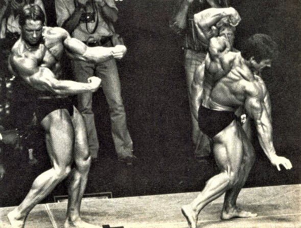 1980 Olympia Arnold posing against Mentzer