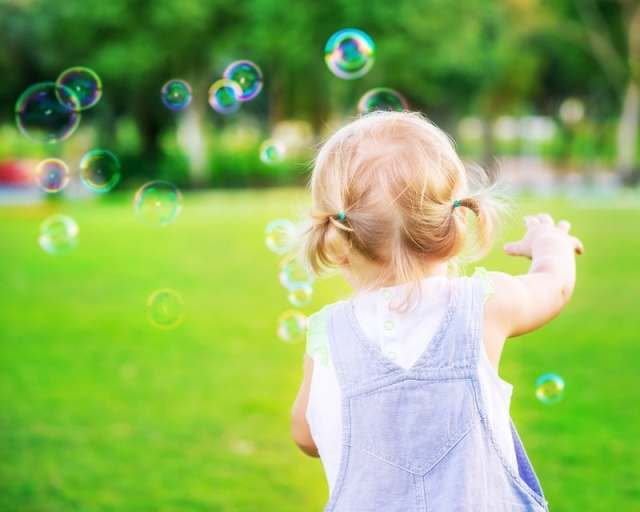 Baby girl play with soap bubbles