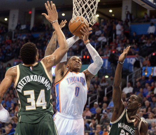 Apr 4, 2017; Oklahoma City, OK, USA; Oklahoma City Thunder guard Russell Westbrook (0) drives to the basket between Milwaukee Bucks forward Giannis Antetokounmpo (34) and guard Tony Snell (21) during the third quarter at Chesapeake Energy Arena. Mandatory Credit: Mark D. Smith-USA TODAY Sports
