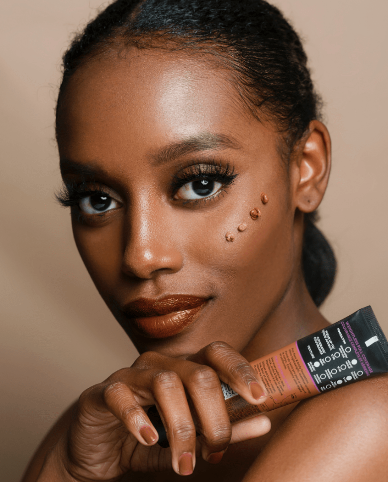 a black woman who is close up to the camera with four dots on her cheek to highlight the beauty product
