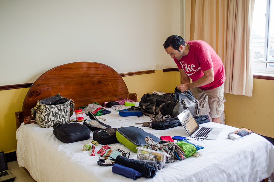 Adrian next to our bed packing our backpacks to leave Battambang, Cambodia.