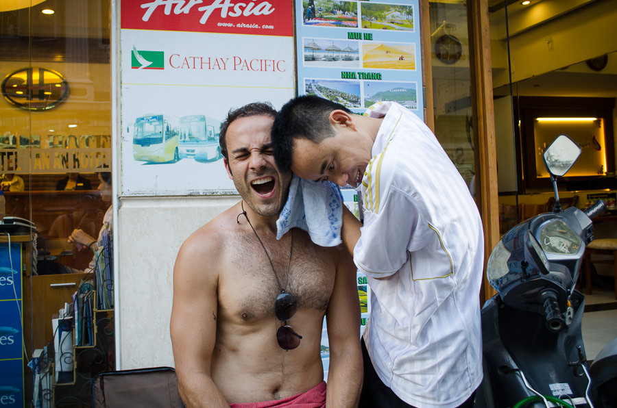 A man getting a massage on the street and obviously in pain.