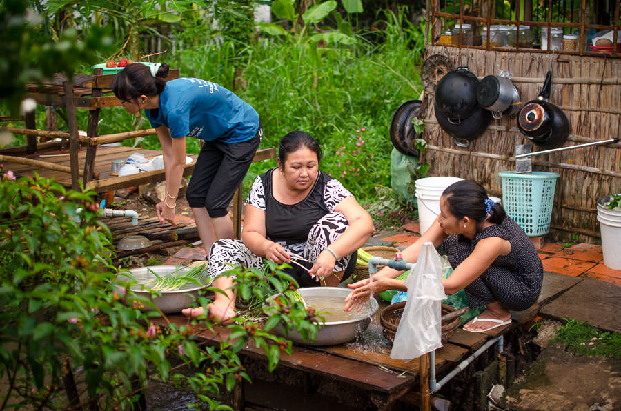 Women cleaning and preparing vegetables for dinner.