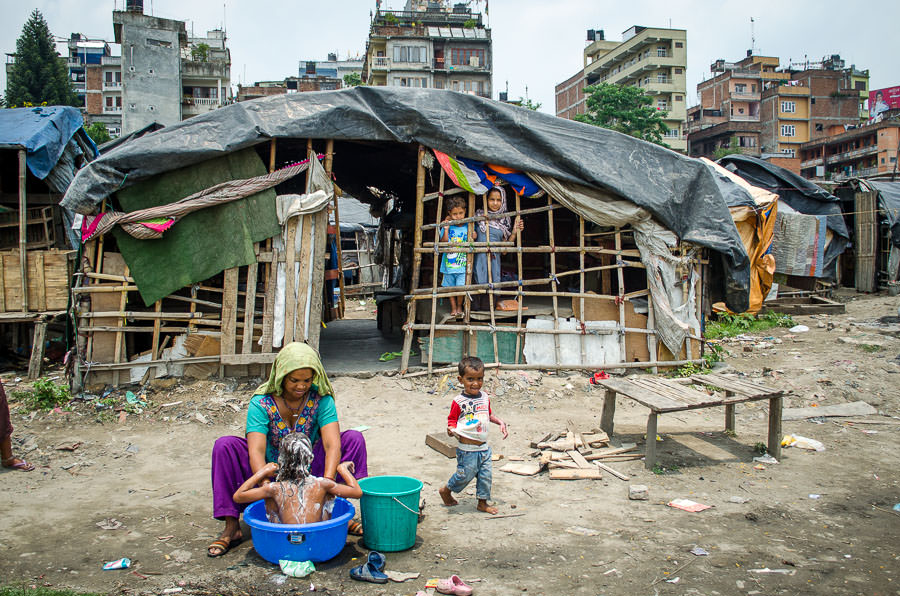 A woman giving her daughter a bath in front of her house in tent city, Kathmandu, Nepal