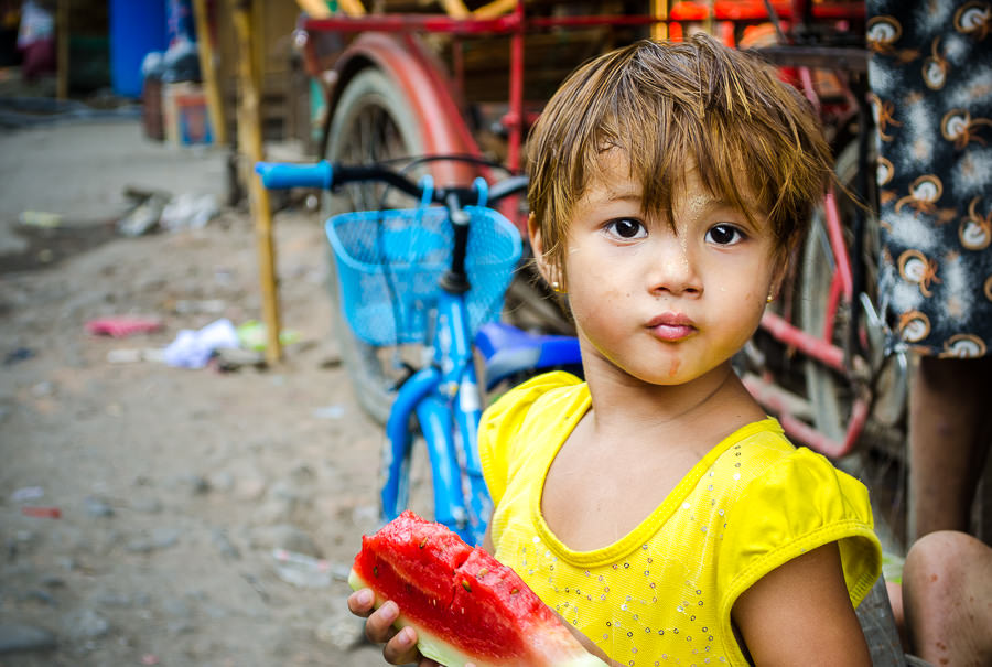 Colors of summer represented by a young girl eating a piece of watermelon.