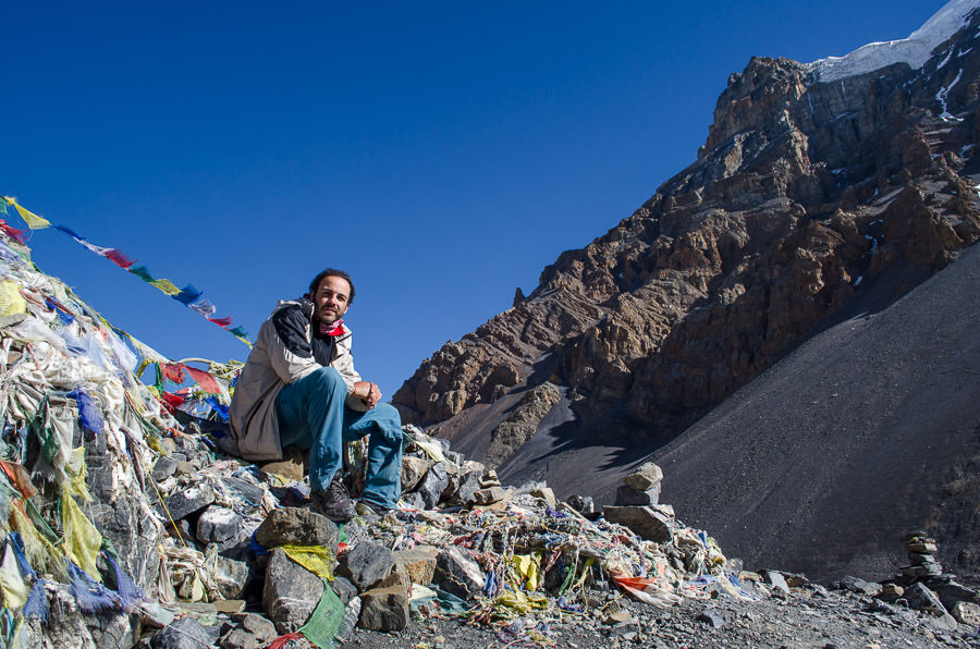 Adrian sitting at the top of the mountain at Thorong-La Pass on the Annapurna Circuit.