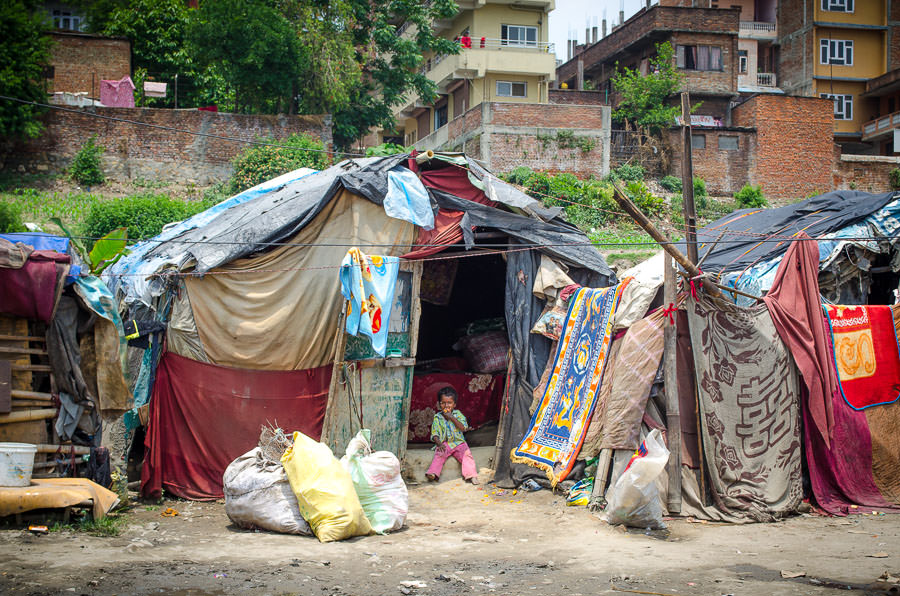 A young girl sits in the doorway of her tent house in Kathmandu, Nepal