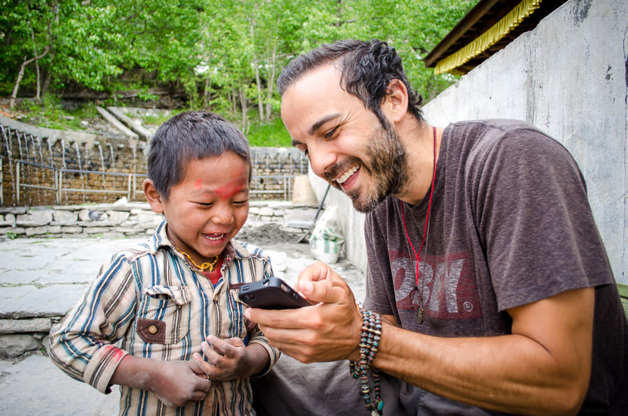 Adrian showing a young boy his photo on the iPhone in Muktinath
