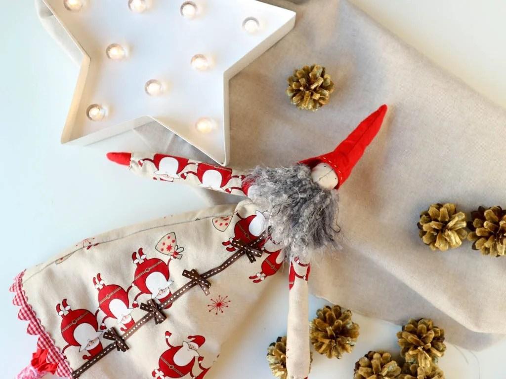 duende de tela, luces de navidad y piñas doradas