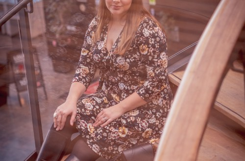 woman in a black flower dress sitting in stairs