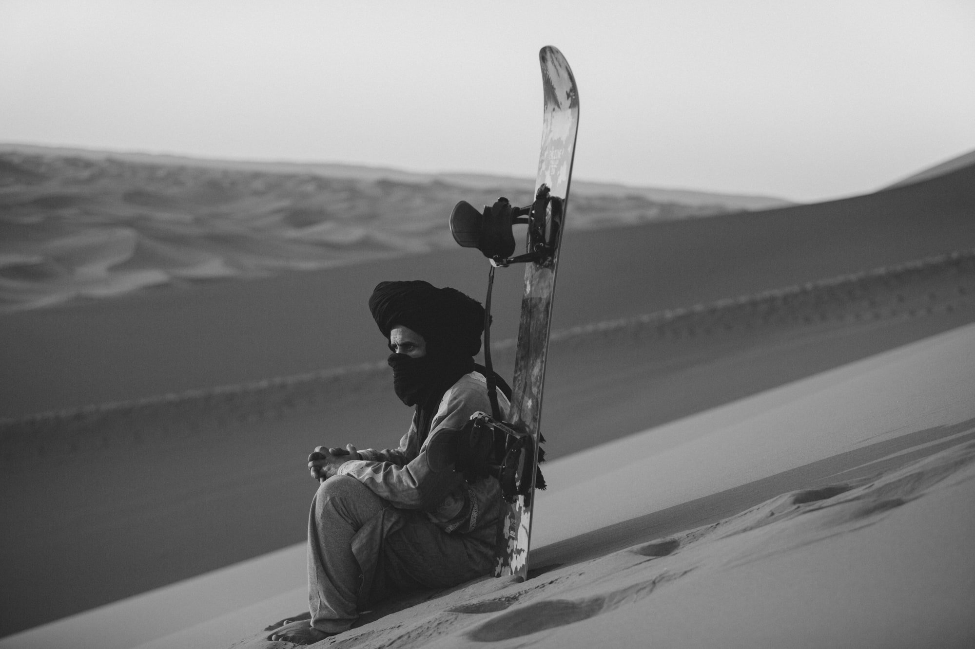 Sandboarding Instructor with Sandboard Sitting on Sand Dune near the Nubia Desert Camp in Morocco