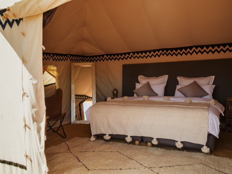 Luxury furnished bedroom with double bed at Nubia Sahara Camp Tent Morocco